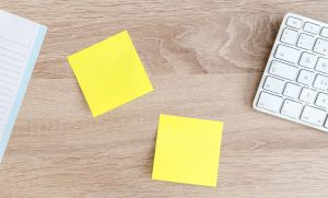 Birds-eye view of notebook, two yellow sticky notes, and a computer keyboard on a wood surface